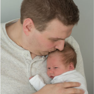 Letting Dads have a seat at the table blog image. Photo of a father kissing his newborn baby on the head.