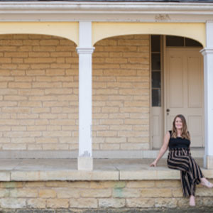 IABA Consultants owner Jessie Topalov sitting on a porch.