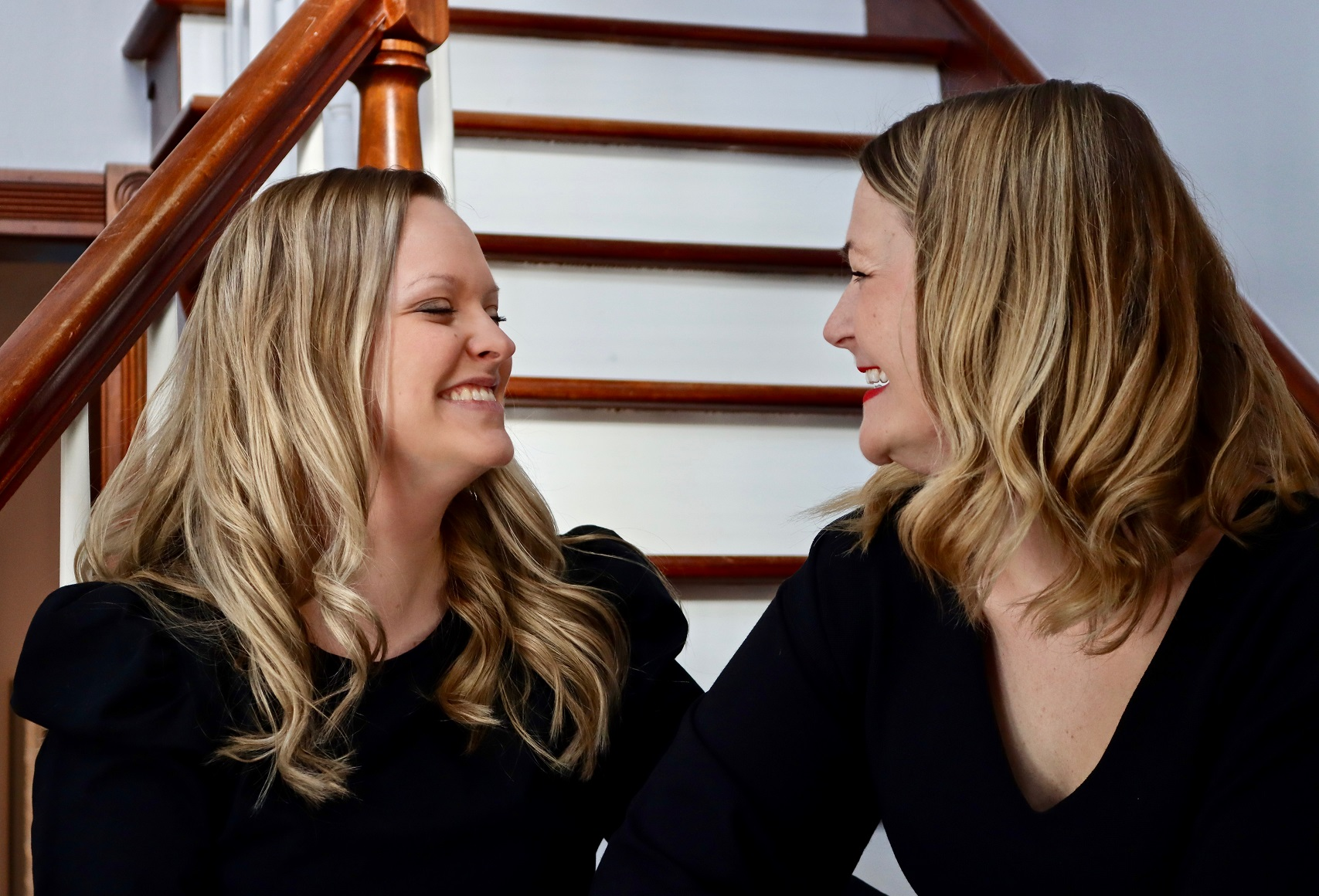 Too Strong for Who? blog featured image. Photo of Jessie and her sister sitting on staircase and sharing a laugh.