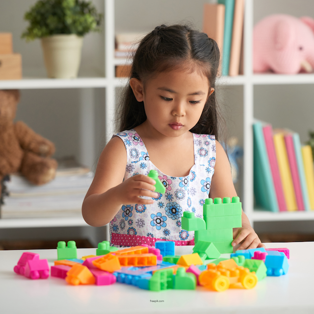 What are the Signs of High Functioning Autism blog image. Photo of a young girl playing with blocks.