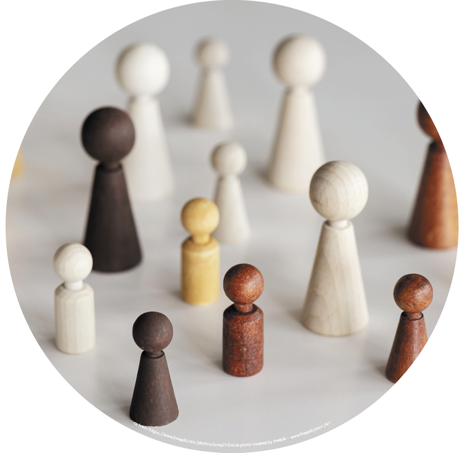 ASD & Gender Comorbidities blog. Image of handcarved wooden people of various sizes & colors.